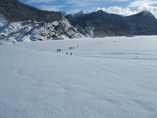 Line of People Trekking Across the Lake