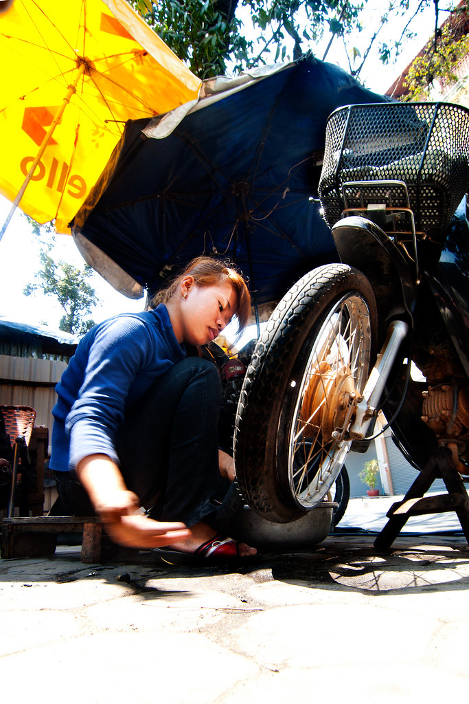 A girl repairing flat tire.