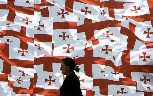 A woman walks past a wall decorated with Georgian national flags in the centre of Tbilisi