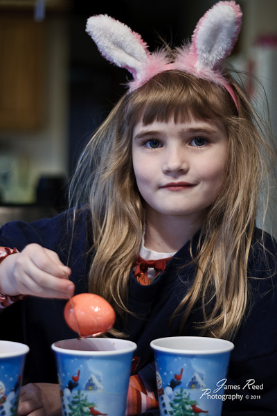 The little one assists the Easter Bunny in coloring eggs.
