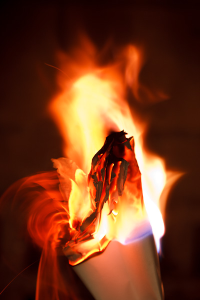 Flames in motion atop a bundle of papers.