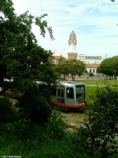 Muni train passes Dolores Park