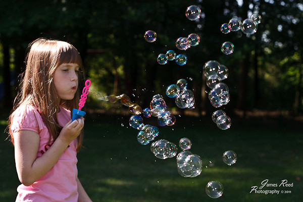 Big one blowing bubbles for her sister and the puppy to chase.