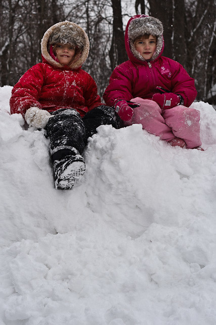 The girls gloat at the top of the snow mound after pushing Daddy off.