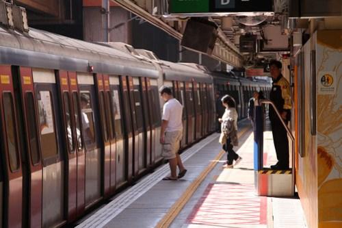 Platform attendant waiting on passengers at Fo Tan station