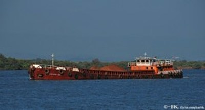 A boat carrying iron ore from a ship to the fa...