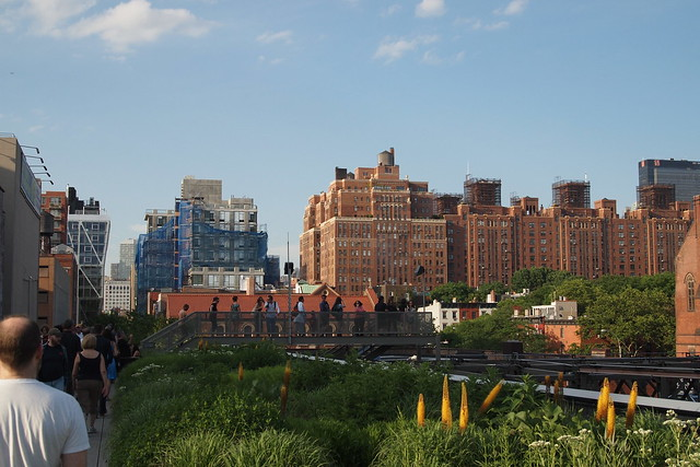 View looking north from the High Line to a block of apartments with scaffolding at the top