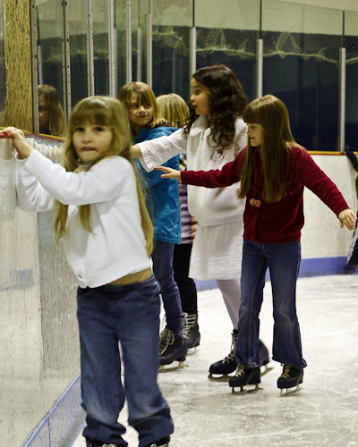 It takes a lot of girls to hold up that rickety ice rink wall...