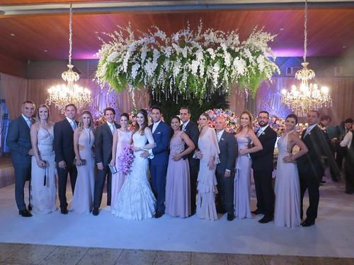 Os noivos com padrinhos e madrinhas, elas seguindo a paleta de cores proposta por Marianna
