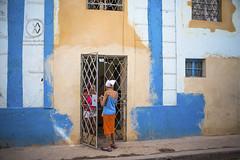 Women talk on the street in Havana.