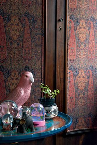 O periquito rosa acende os olhos quando toca. A peça rara é o telefone da casa e fica num canto do escritório