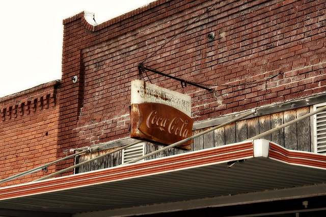 Rusting old Coca-Cola sign on storefront in Commerce, OK. Route 66 photo copyright Jen Baker/Liberty Images; all rights reserved.