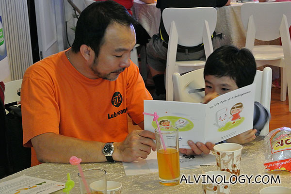 A father reading a Panasonic eco book on Fridges to his little son