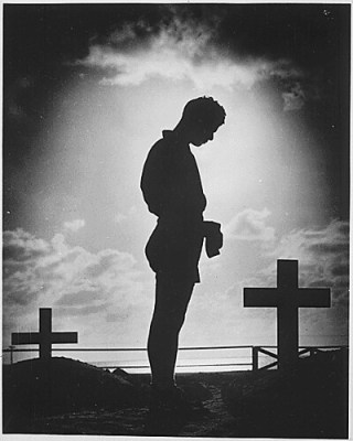 A Coast Guardsman stands in silent reverence beside the resting place of a comrade., 1944
