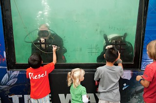 EOD technicians play tic-tac-toe with a children at a family day picnic
