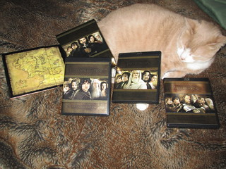 Photo of a cat with complete set of Lord of the Rings blu-ray dvds