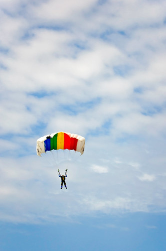 Parachute jumper descending on cloudy day