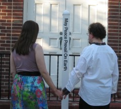 The Peace Couple contemplate The Peace Pole