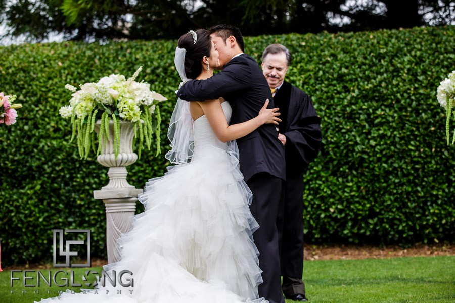 Chinese bride and groom kiss during wedding ceremony