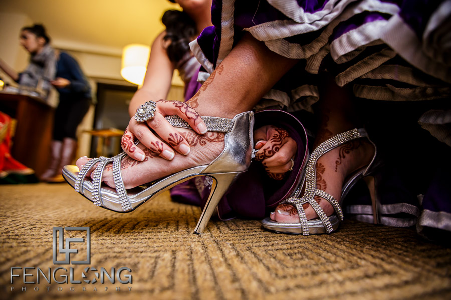 Kanwal has help putting on her shoes for the wedding reception of their Atlanta Ismaili Indian wedding