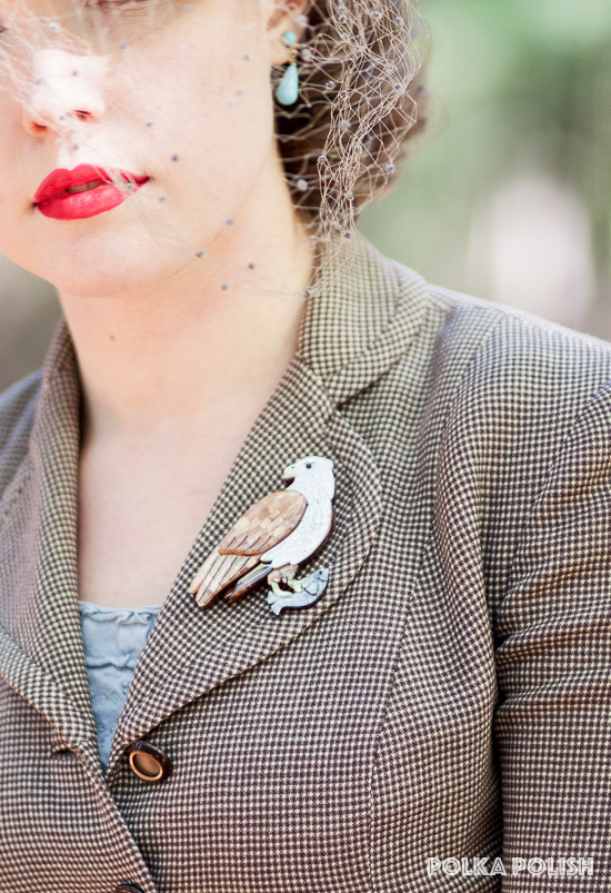 Large resin brahminy kite brooch from Erstwilder makes a stunning accent on the apel of a checked 1940s suit jacket in cream and brown