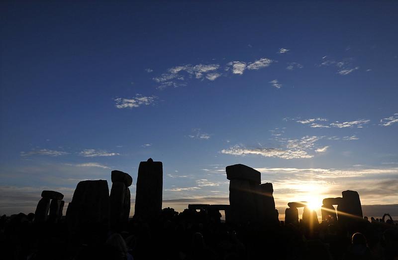 The sun rises behind Stonehenge.
