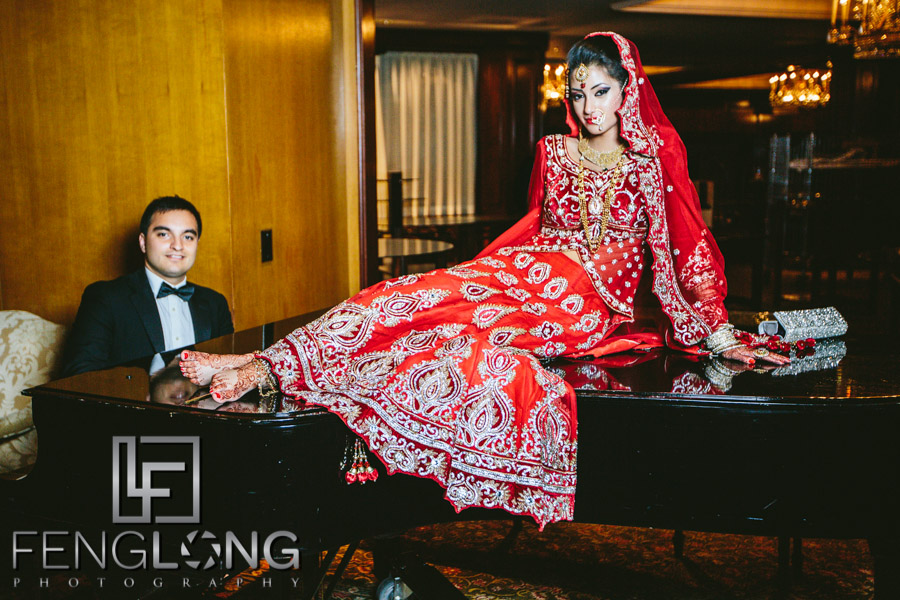 Bride sits on piano while groom plays at the Ritz-Carlton Buckhead