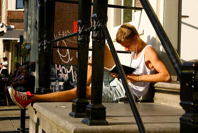 Cute boy reading on the street.