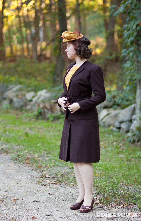 A vintage autumn ensemble featuring a brown 1940s suit with a goldenrod tilt hat and sweater and brown Royal Vintage Shoes Dolores pumps