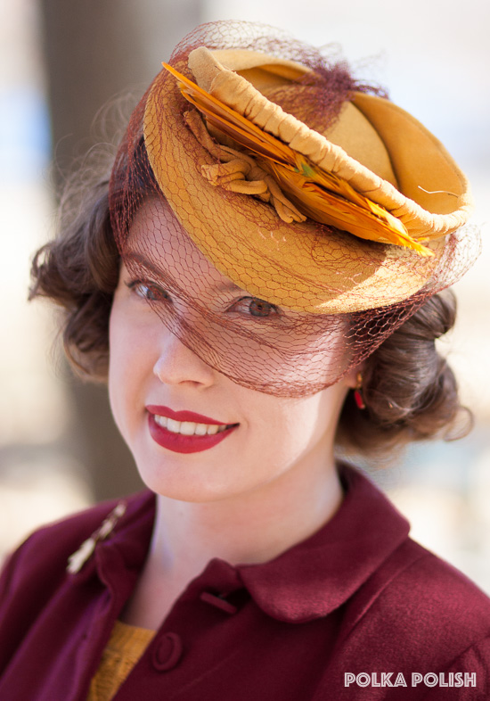 A dramatic feathered 1940s tilt hat covered in yellow jersey with rust colored netting is a perfect finishing touch with a vintage suit