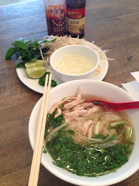 Bowl of Pho Ga chicken noodle soup with fresh Thai Basil, bean sprouts, onions and lime