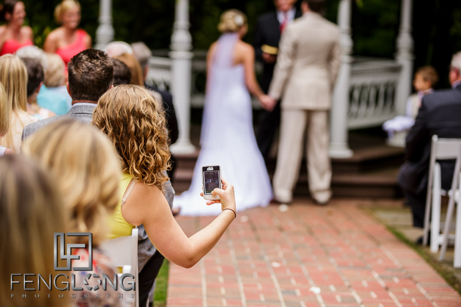 Guest takes a photo of the wedding ceremony with a smartphone