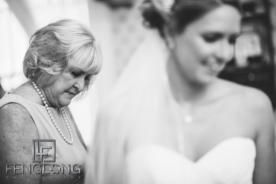Bride's mother helping per on her wedding dress