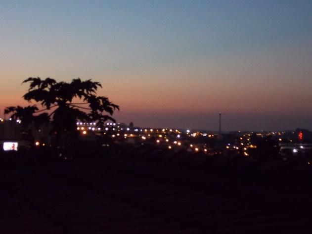 O céu ainda não se apagou, mas a cidade já se acendeu.