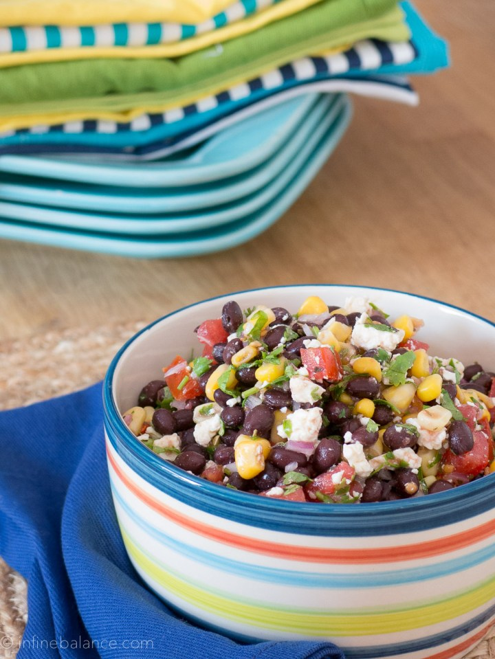 black bean and corn salsa with feta and tomatoes in a blue triped bowl