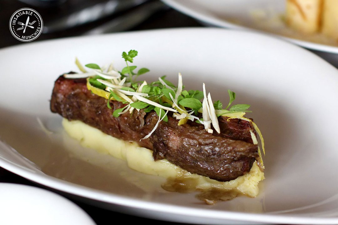 Tender braised beef short ribs are slow cooked, removed from the bone, and served on a bed of creamy mash.
