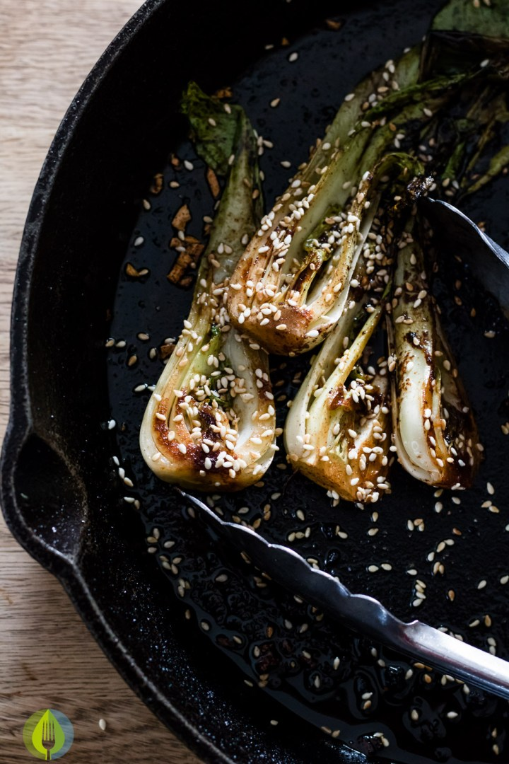 overhead view of skillet sauted bok choy with spicy sauce and sesame seeds in a cast iron skillet