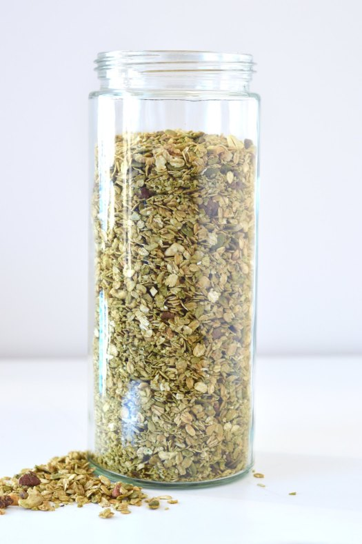 Maple matcha granola in a large glass jar.