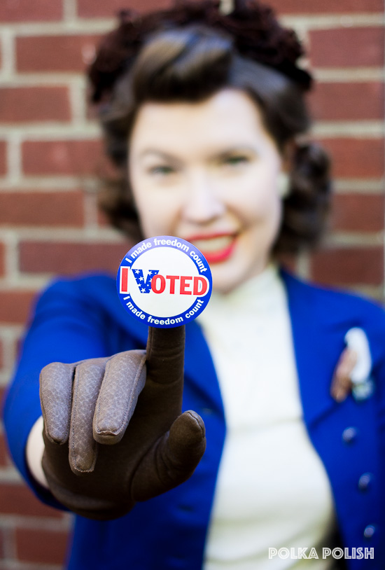 "An ""I Voted!"" sticker is proudly displayed in the foreground by a woman wearing a patriotic colored vintage 1940s jacket and hat"