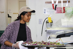 Trisha Dalapati carefully sets the vegetables on the counter after removing them from the oven at Talmage Terrace for Campus Kitchen on Feb. 12, 2019. (Photo/Paige Watkins)