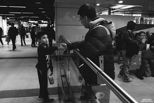 晚上的台北火車站剪票口,我見到了隔代養育的情懷,照片中的爸爸收假要搭車回去工作,而兩個兒子也由阿公阿嬤帶著前來相送,準備下到月台搭車時,兩人分隔在剪票口內外,爸爸一直牽著兒子的手,或者是說放開了,卻又立馬牽起,重覆了好幾次,一邊交待著他要好好照顧自己跟弟弟。父子情懷難得一見(有點鼻酸)。