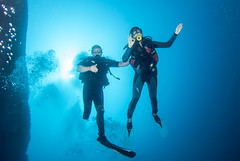 BK amputee diving instructor accompanies a novice diver underwater