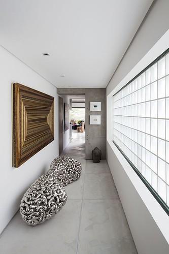 Galeria de passagem para a sala, com obra de arte de Marcello na parede, molduras sobre molduras