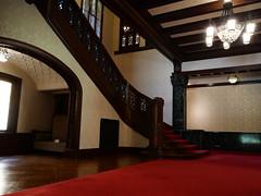 玄関広間から二階への大階段と下に設けられたイングルヌック