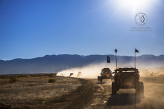 A group of off road vehicles line up to race across the desert.