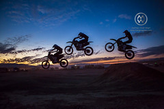 A motorcyclist jumps into the air at sunset.