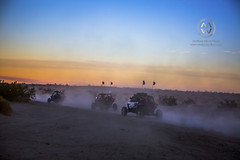 A group of off road vehicles line up to race across the desert in sunset.