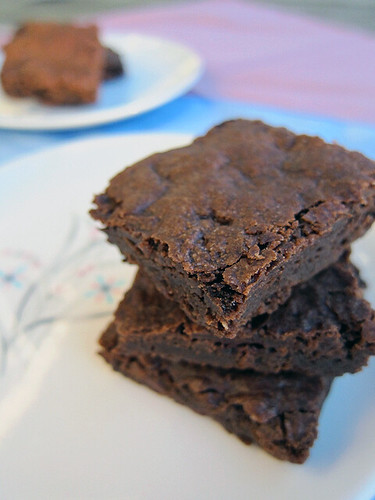 A photo of three brownies stacked on a plate; they're obviously fudgy and have a crackly top layer!