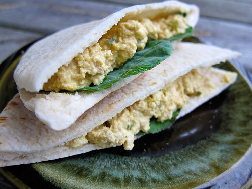 Two pitas stacked on top of each other, filled with a light yellow crumbled tofu and a couple collard leaves.