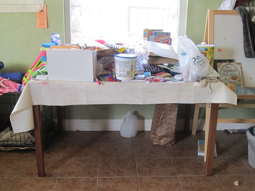 kitchen table, currently piled with junk